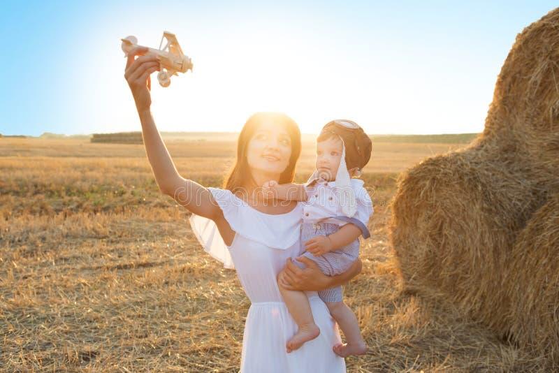 使用与在春天领域的玩具飞机的母亲和她的孩子在软的阳光 免版税库存图片