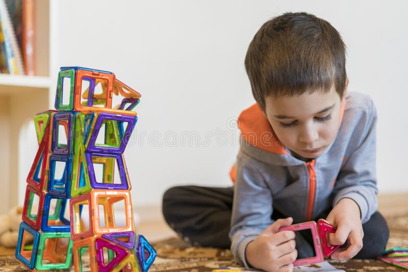 使用与磁性建设者玩具的小微笑的男孩 演奏智力玩具的男孩 库存照片