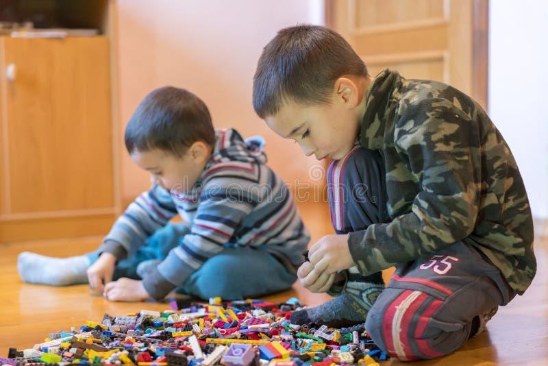 使用与许多的两个孩子五颜六色的塑料块建设者坐室内地板 两个弟弟戏剧 免版税库存照片