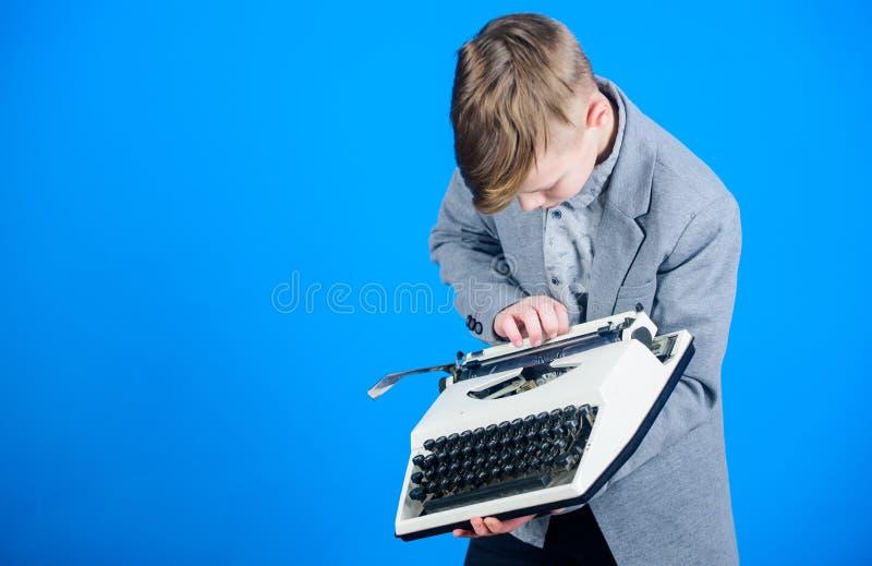 使用一台打字机 打字在老打字机的小孩子 有葡萄酒打字机的聪明的男小学生 逗人喜爱的男孩与 免版税库存图片