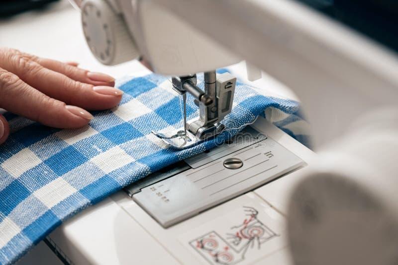使用一台缝纫机的妇女的手 库存图片