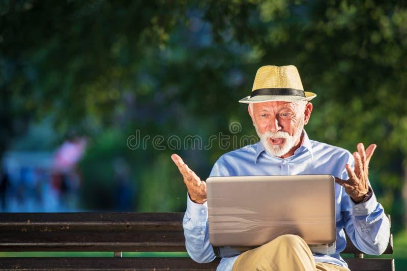 使用便携式计算机的老人休息在公园户外 免版税库存照片