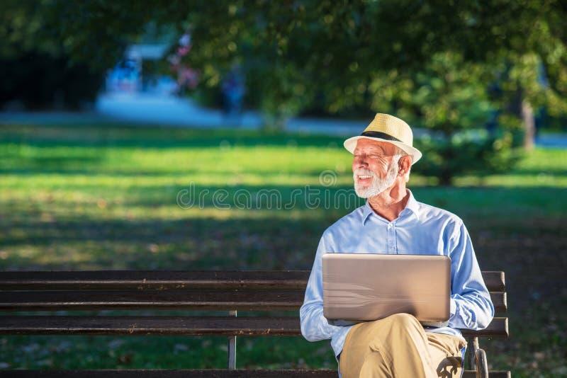 使用便携式计算机的老人休息在公园户外 库存照片