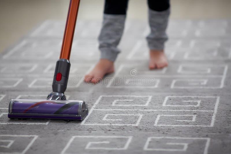 使用吸尘器的男孩,当清洗地毯在房子时 库存图片