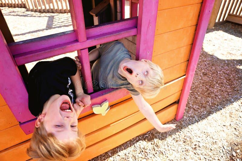 使用外面在俱乐部议院里的两个逗人喜爱的小孩在操场,做滑稽的面孔 免版税库存照片