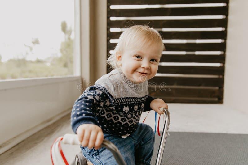 使用外面在木玩具自行车滑行车机动性的珍贵的可爱的逗人喜爱的矮小的白肤金发的小小孩男孩孩子微笑对来了 免版税图库摄影