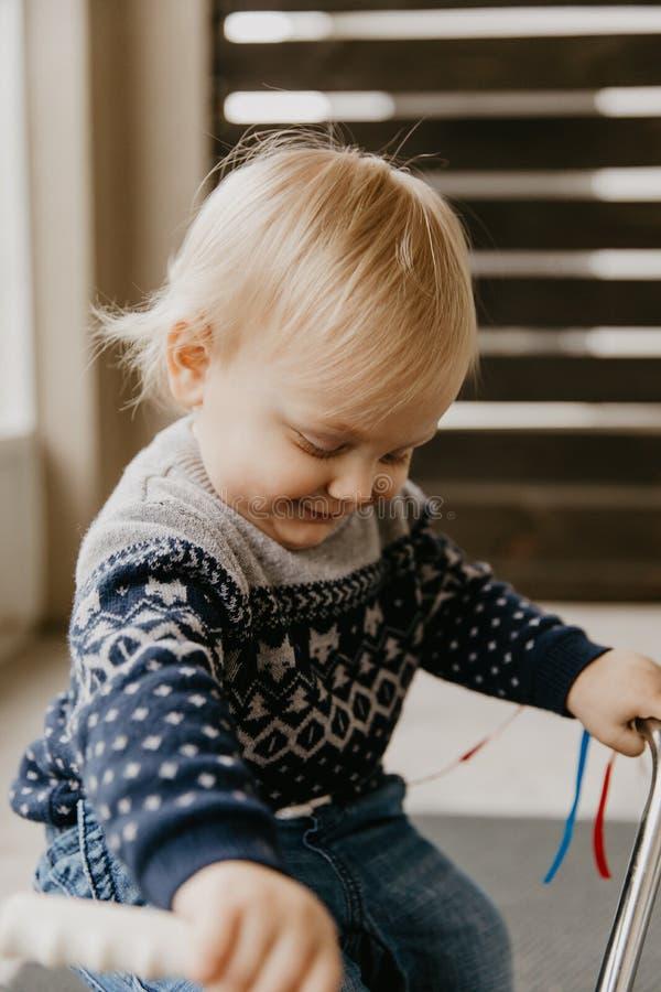 使用外面在木玩具自行车滑行车机动性的珍贵的可爱的逗人喜爱的矮小的白肤金发的小小孩男孩孩子微笑对来了 免版税库存照片