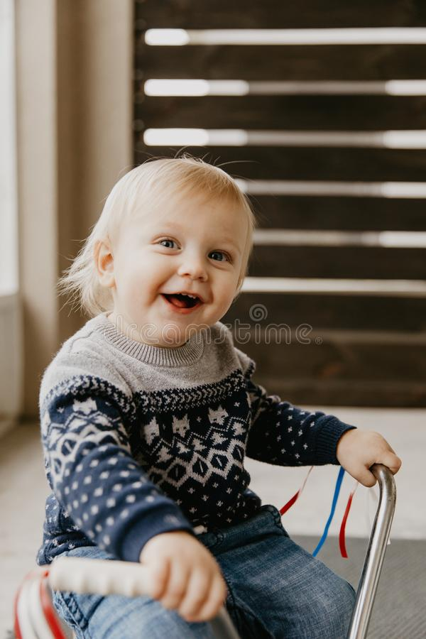 使用外面在木玩具自行车滑行车机动性的珍贵的可爱的逗人喜爱的矮小的白肤金发的小小孩男孩孩子微笑对来了 库存照片
