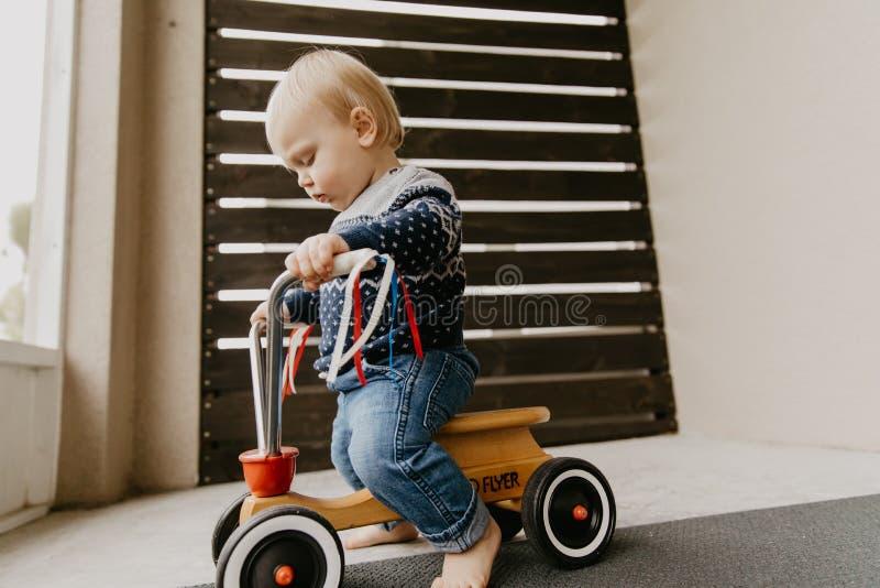 使用外面在木玩具自行车滑行车机动性的珍贵的可爱的逗人喜爱的矮小的白肤金发的小小孩男孩孩子微笑对来了 免版税库存图片