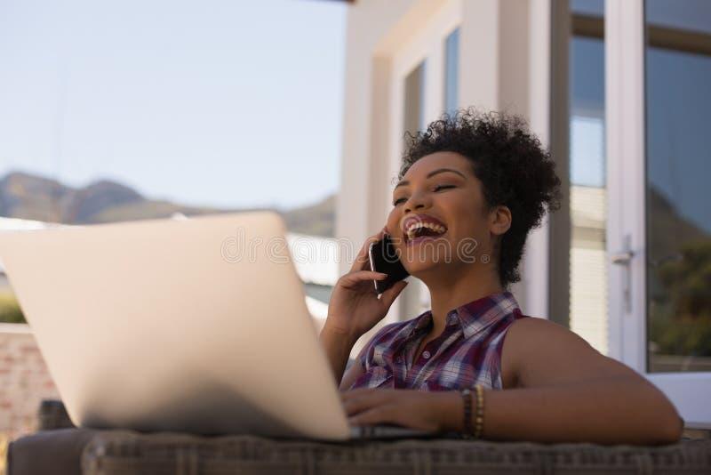 使用在大阳台时的膝上型计算机美女谈话在手机,当 免版税库存图片