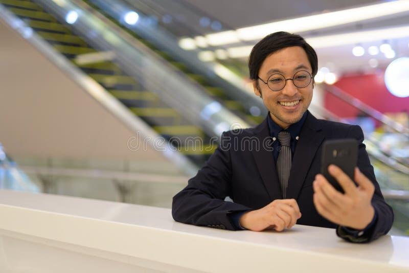 使用在办公楼里面的愉快的亚洲商人电话 免版税库存照片