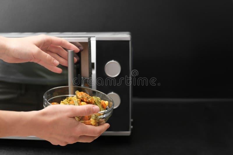 使用在桌上的年轻女人微波炉在厨房 免版税库存图片
