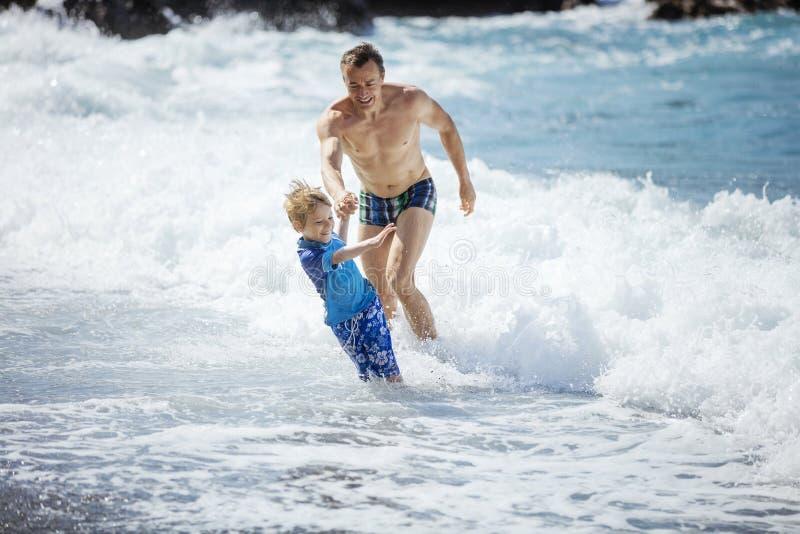 使用在汹涛的海滩的父亲和儿子 免版税图库摄影