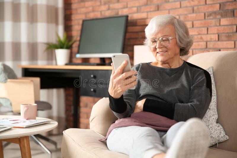 使用在沙发的年长妇女智能手机 免版税库存照片