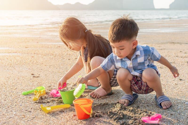 使用在海海滩的逗人喜爱的矮小的亚裔孩子在夏天在泰国 免版税库存图片