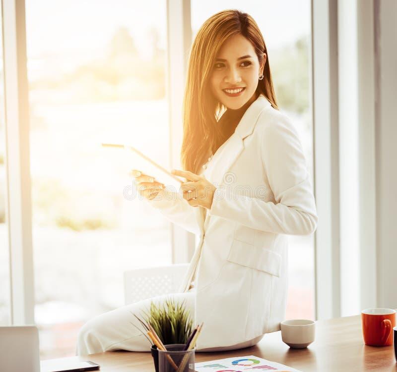 使用在早晨窗口办公室前面的可爱的女实业家一种数字片剂 免版税库存图片