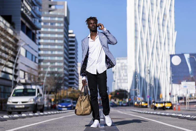 使用在晴朗时的电话走在街道上的一非洲黑人年轻人的正面图穿典雅的夹克和拿着袋子,当 免版税库存照片