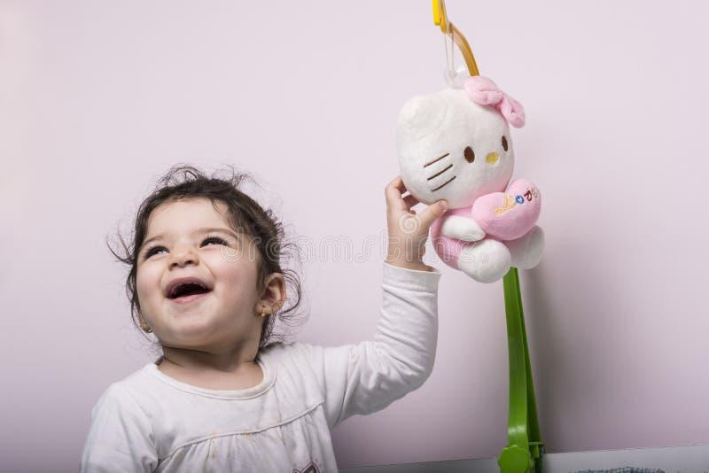 使用和享用与她的在桃红色墙壁前面的玩偶的愉快的女孩 免版税库存照片