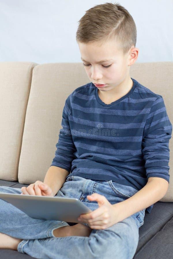 使用数字平板电脑的青少年的男孩 打比赛或在家检查在片剂的年轻男孩社会媒介 互联网网上教育 库存照片