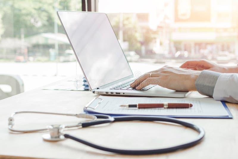 使用数字手提电脑医疗运作的信息的医生与在书桌上的听诊器在办公室医院 图库摄影