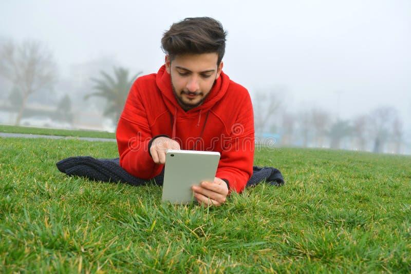 使用数字片剂的年轻人在公园 免版税库存图片