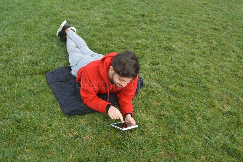 使用数字片剂的年轻人在公园 库存照片