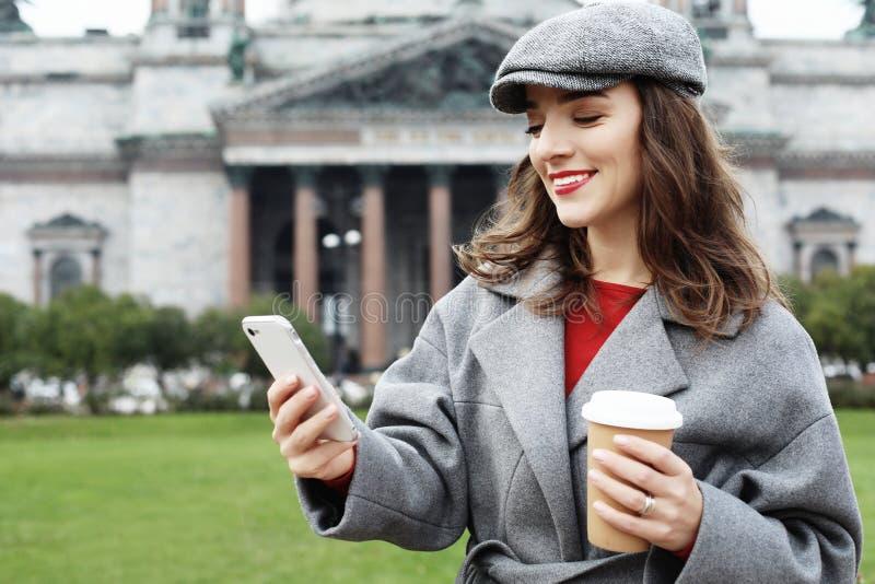 使用手机的一名相当微笑的妇女的画象,当拿着在城市街道上时的咖啡杯 库存照片