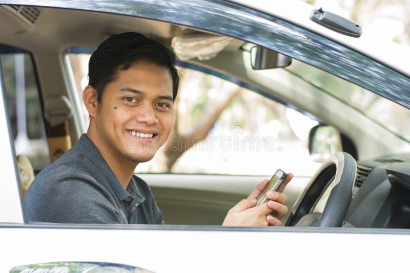 使用手机的年轻可爱的愉快的亚洲男性和看照相机,当驾驶他的汽车在好日子时 免版税库存照片