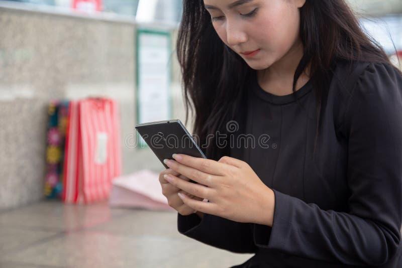 使用手机的美女在与购物带来的mallÂ在背景 拿着手机的亚裔少女做购买 免版税图库摄影