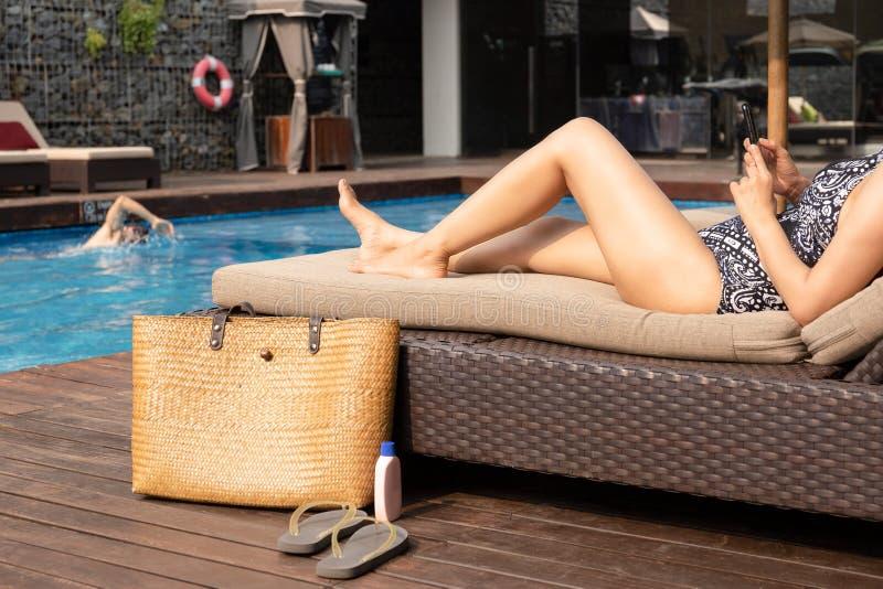 使用手机的花姑娘说谎在椅子由有海滩袋子的游泳场 库存照片