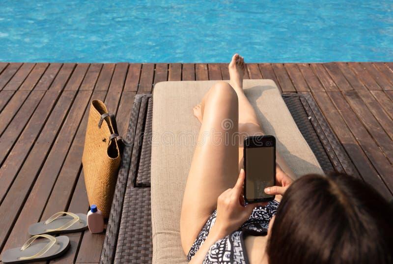 使用手机的花姑娘说谎在椅子由有海滩袋子的游泳场 图库摄影