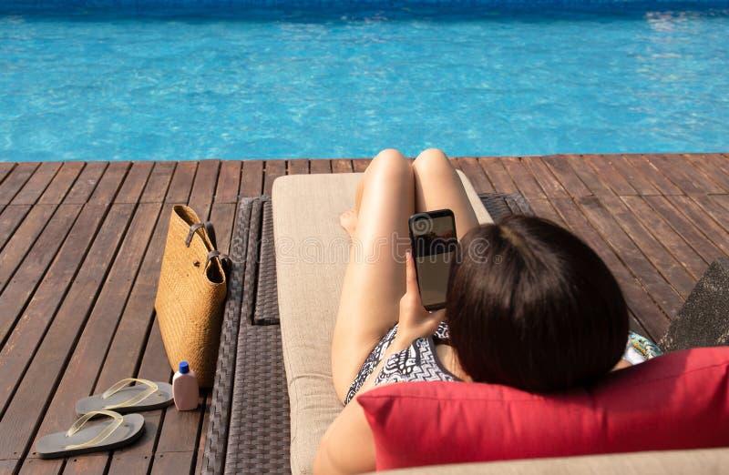 使用手机的花姑娘说谎在椅子由有海滩袋子的游泳场 免版税图库摄影