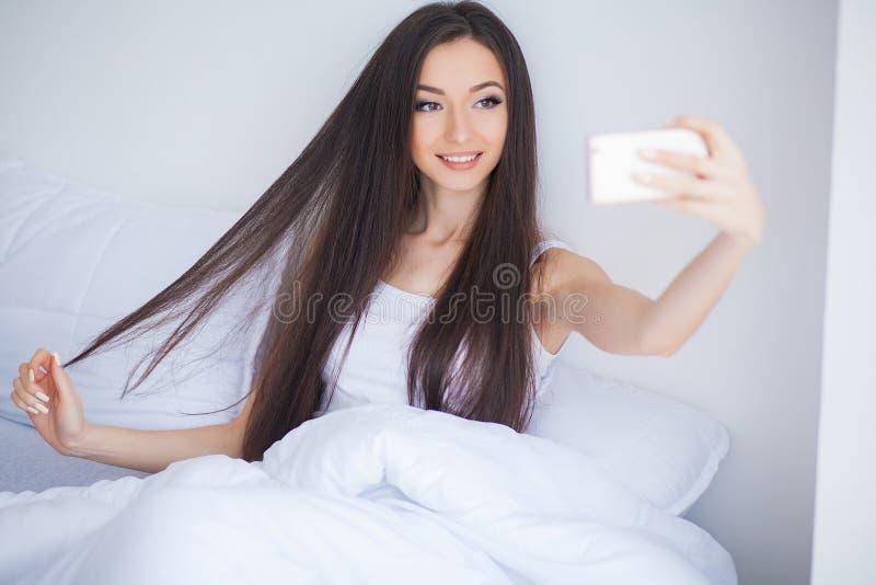 使用手机,愉快的逗人喜爱的妇女射击在床上说谎 库存照片