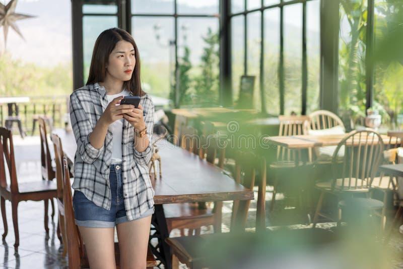 使用智能手机的妇女在咖啡馆 免版税库存照片