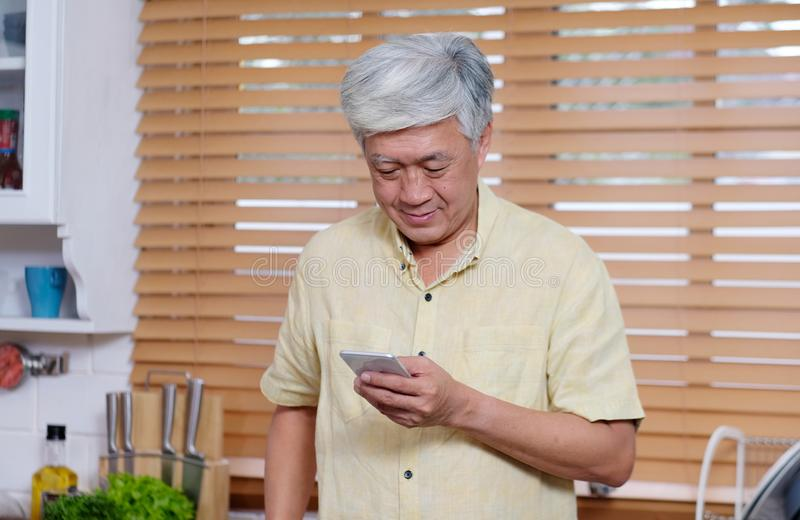 使用智能手机的资深亚裔人,当在家站立在厨房,人和技术里时 库存图片