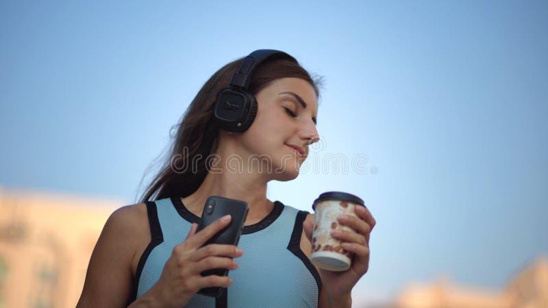 使用智能手机,键入的消息的美丽的年轻女人,听到音乐,饮用的咖啡,当走在都市时 免版税图库摄影