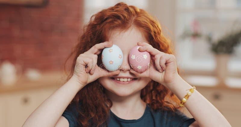 使用用在厨房背景的复活节彩蛋的快乐的红头发人小孩女孩画象  她欢呼和 库存照片