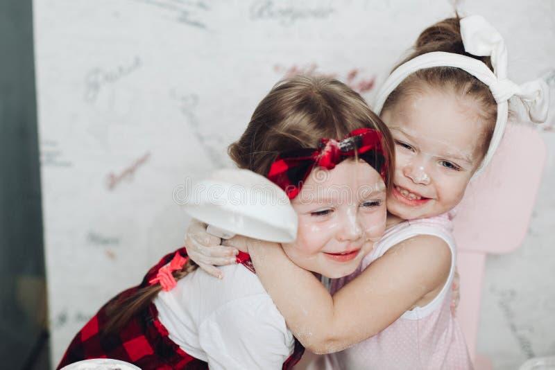 使用用面粉和拥抱在厨房的可爱的姐妹 免版税库存照片