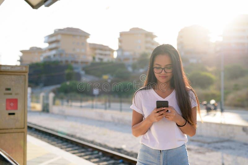 使用电话的年轻美丽的亚裔旅游妇女在火车站 免版税库存照片
