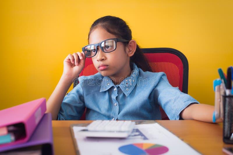 使用计划工作想法的逗人喜爱的女孩戴着眼镜在书桌有文件被隔绝的黄色背景 库存照片