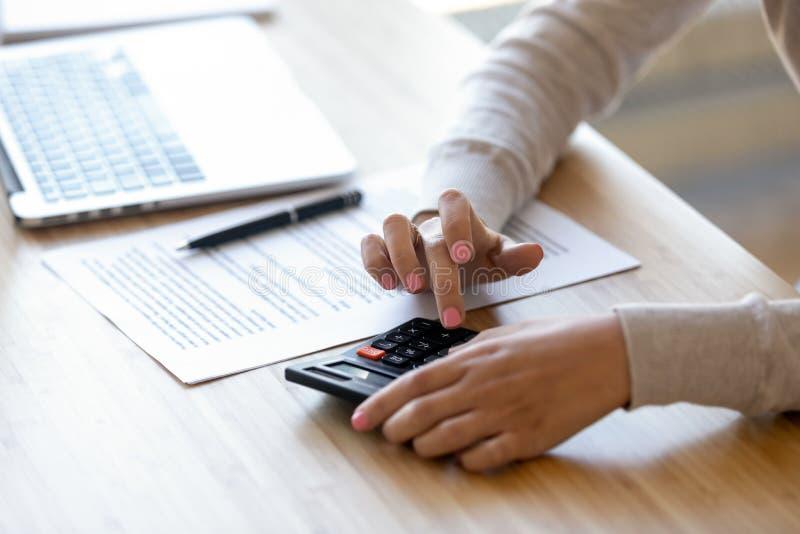 使用计算器的接近的年轻女人,计算财务在工作场所 库存照片