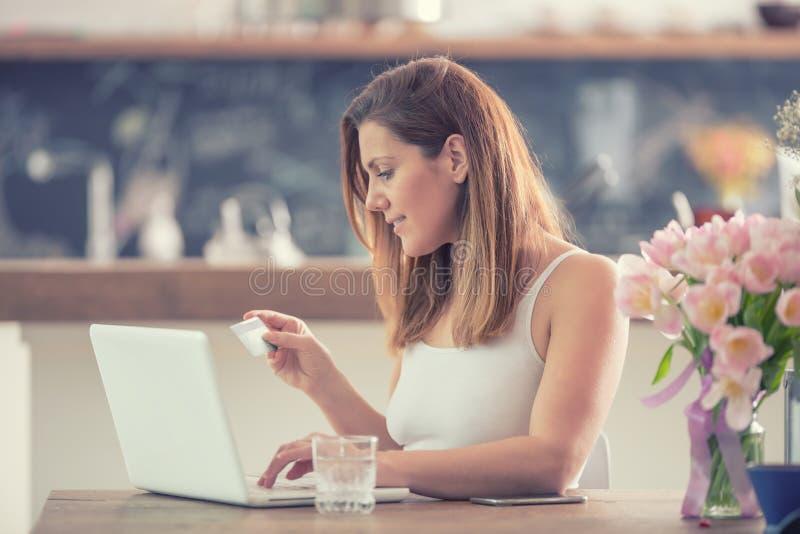 使用计算机和信用卡的有吸引力的年轻女人网络购物在家庭厨房里 免版税库存照片