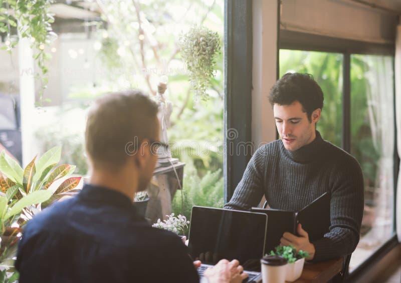 使用膝上型计算机的两个商人在会议上在咖啡馆 图库摄影
