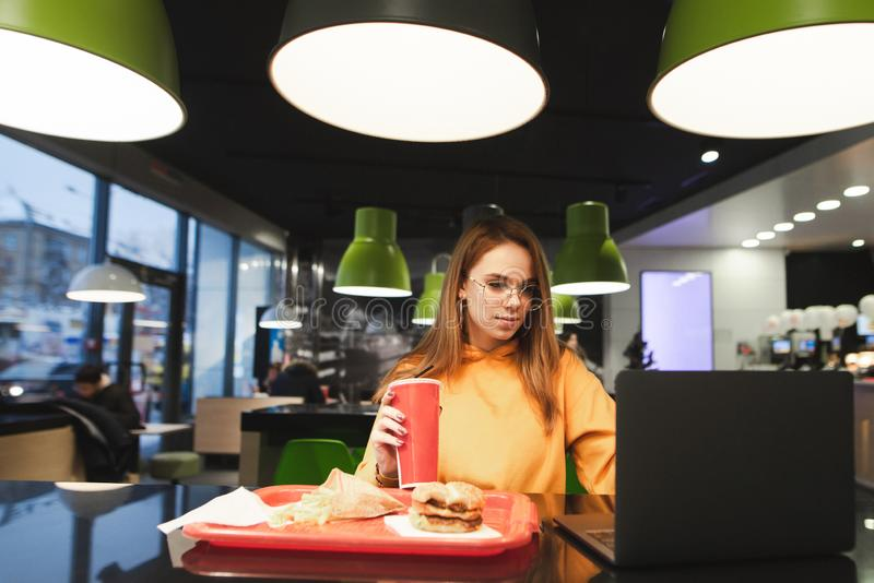 使用膝上型计算机的一时髦的可爱的年轻女人的画象在一个舒适咖啡馆和吃便当 免版税库存照片