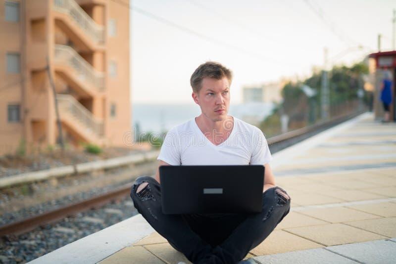 使用膝上型计算机的年轻体贴的旅游人,当坐在火车站时 库存照片