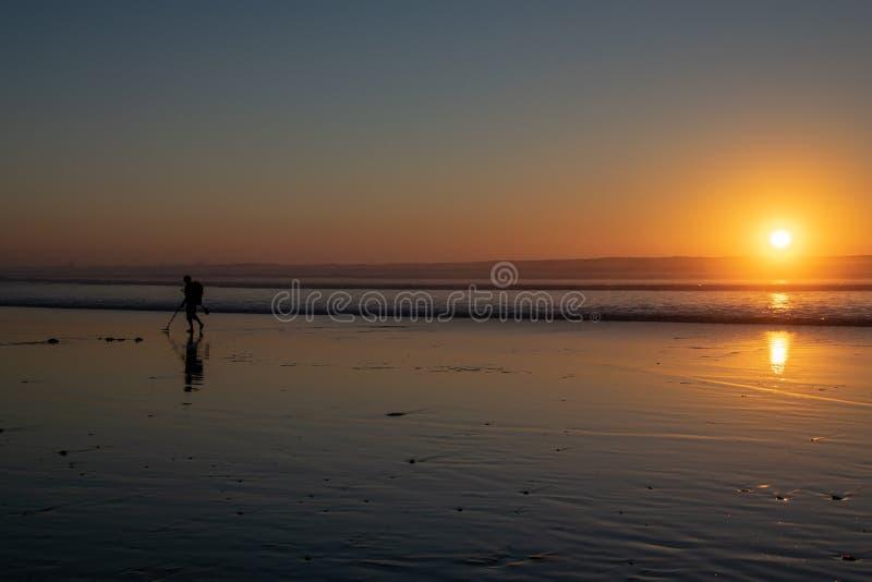 使用金属探测器搜寻在海滩的暗藏的珍宝在日落 免版税库存照片
