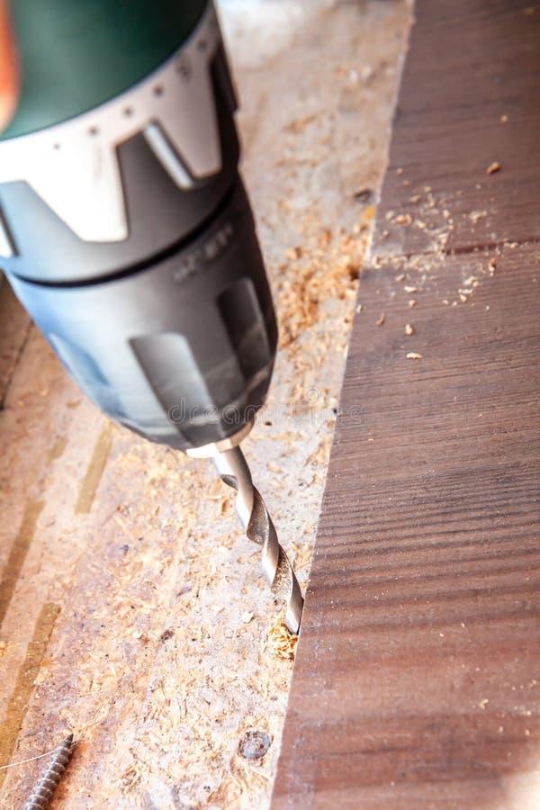 使用钻子机器的人,当在家时安装新的木层压制品的地板 库存照片