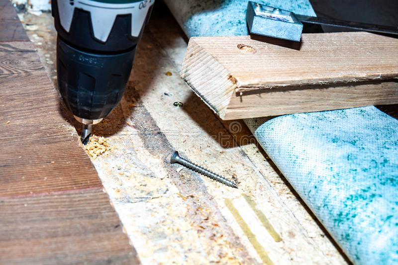 使用钻子机器的人,当在家时安装新的木层压制品的地板 免版税库存图片