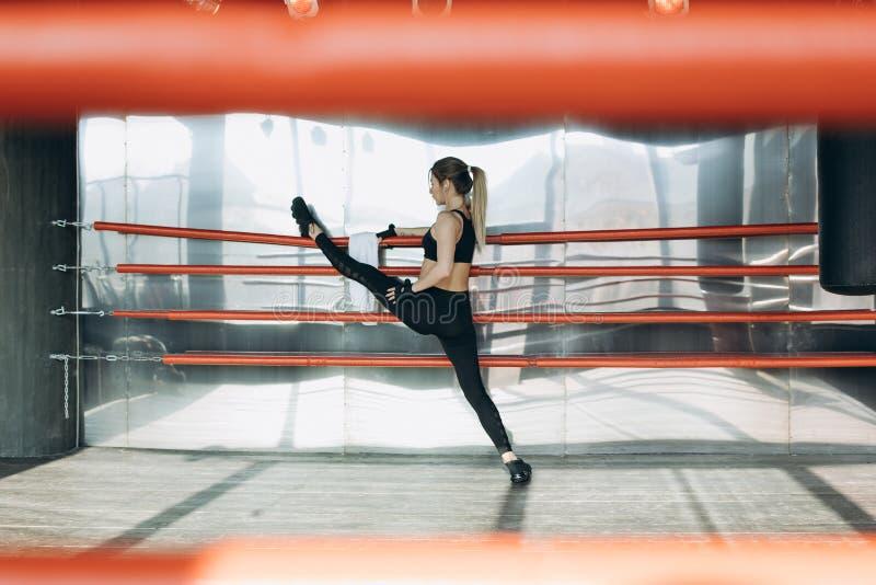 作为她的发怒健身一部分,运动美女做俯卧撑,建身的健身房 免版税库存图片