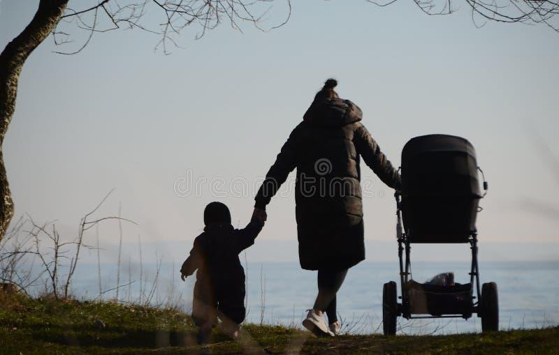 作为剪影和孩子被看见的母亲 免版税库存照片